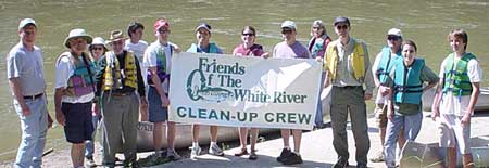 people holding logo banner on riverbank