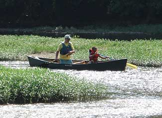 adult and child paddling a canoe
